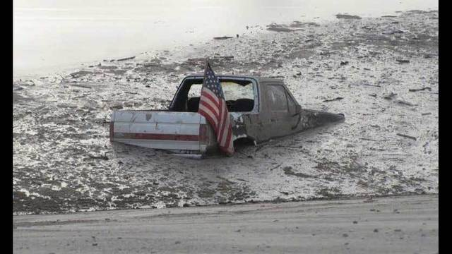 Vehicle buried in mud after driving in flood basin